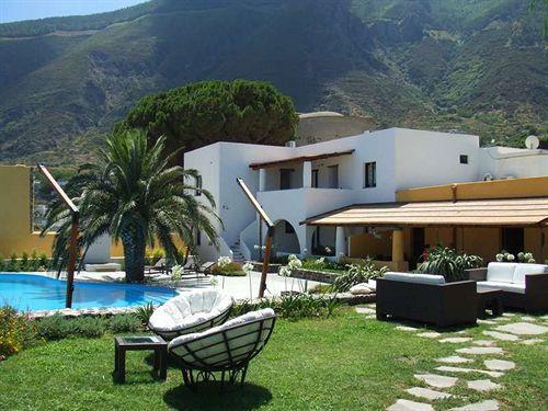 Озеленённая территория отеля ''Ravesi''  с бассейном и плетёной мебелью